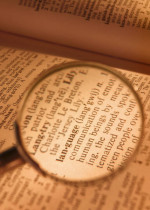 A magnifying glass magnifying the word language in a book