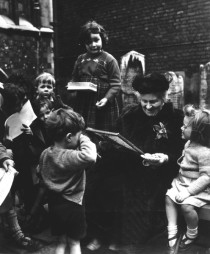 Photo of Maria Montessori sitting surrounded by children in the 1950s
