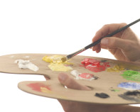 A painting palette with different color paints on it being mixed by an artist