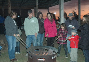 QCMS Parents and Students roasting hot dogs over a fire pit