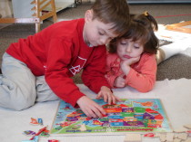 Two pre-school students working together on a puzzle